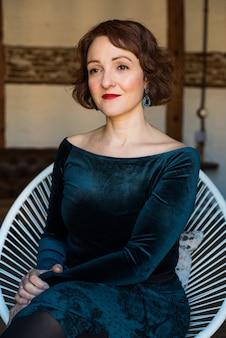 Retrato de uma mulher madura, sentada na cadeira posando pensativo