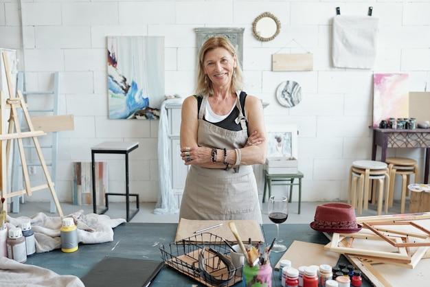 Retrato de uma mulher madura sorridente de avental em pé com os braços cruzados em um estúdio de arte com fotos na parede