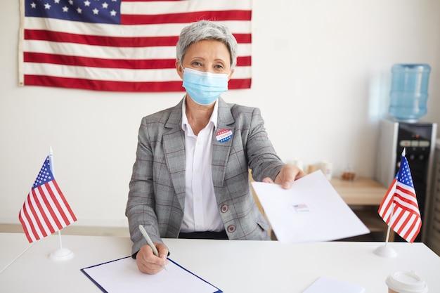 Retrato de uma mulher madura sorridente entregando papéis às pessoas enquanto registra os eleitores na seção eleitoral no dia da eleição, copie o espaço