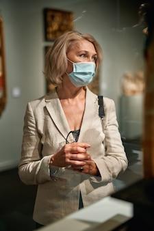 Retrato de uma mulher madura visitando um museu ou galeria usando uma máscara antivírus