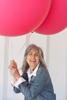 Retrato de uma mulher mais velha posando com uma jaqueta jeans e segurando balões cor de rosa