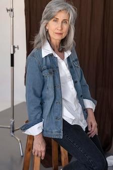 Retrato de uma mulher mais velha posando com uma jaqueta jeans