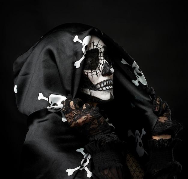 Retrato de uma mulher maquiada com um esqueleto, vestida com uma capa preta e um boné