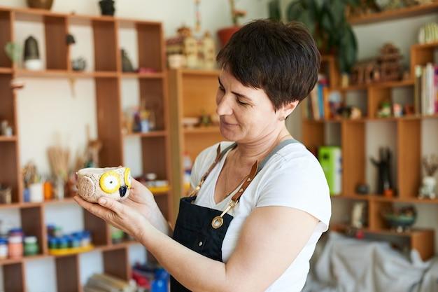 Retrato de uma mulher mestre de cerâmica mostrando a obra acabada.
