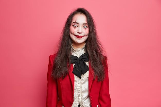 Retrato de uma mulher morena assustadora usando maquiagem gótica de halloween e imagens de um vampiro assustador indo para a festa com poses de olhar horrível contra uma parede rosada