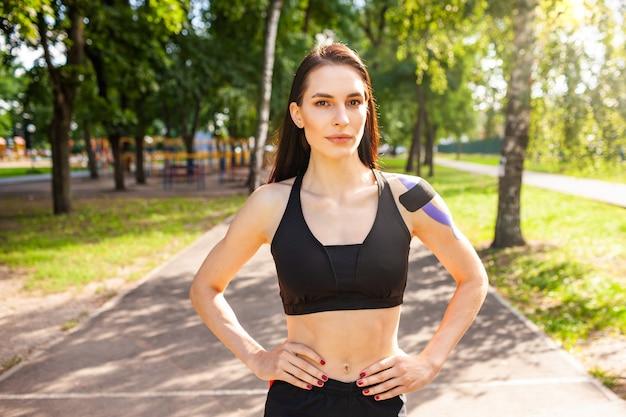 Retrato de uma mulher morena atraente e musculosa, vestindo roupa esportiva preta