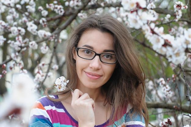 Retrato de uma mulher morena caucasiana sorridente no jardim da árvore de flor de cerejeira na primavera