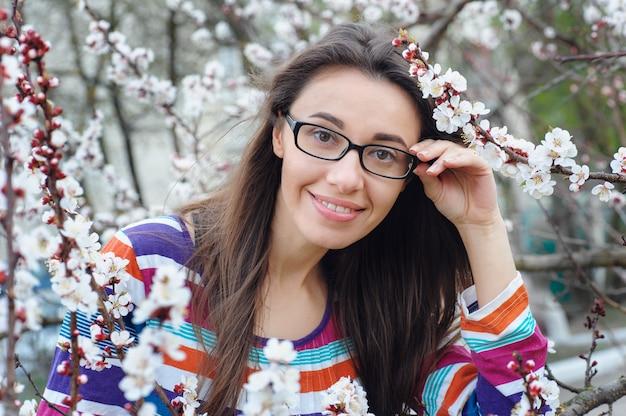 Retrato de uma mulher morena caucasiana sorridente no jardim de árvore de flor de cerejeira na primavera