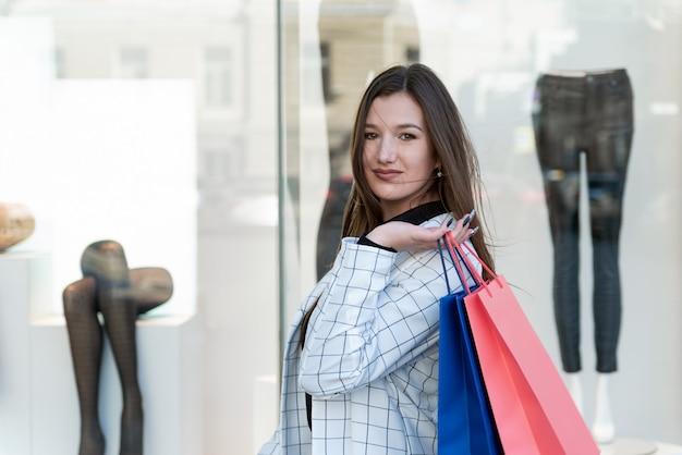 Retrato de uma mulher morena com pacotes coloridos nas mãos, na superfície de vitrine da loja de roupas.