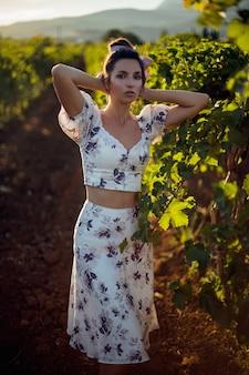 Retrato de uma mulher morena com um vestido branco fica em um vinhedo no verão na itália