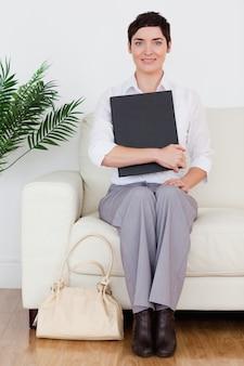 Retrato de uma mulher morena de cabelos curtos sentada em um sofá