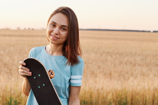 Retrato de uma mulher morena encantadora, vestindo camiseta azul, olhando diretamente para a câmera, segurando o skate nas mãos, copie o espaço para propaganda, estilo de vida saudável.