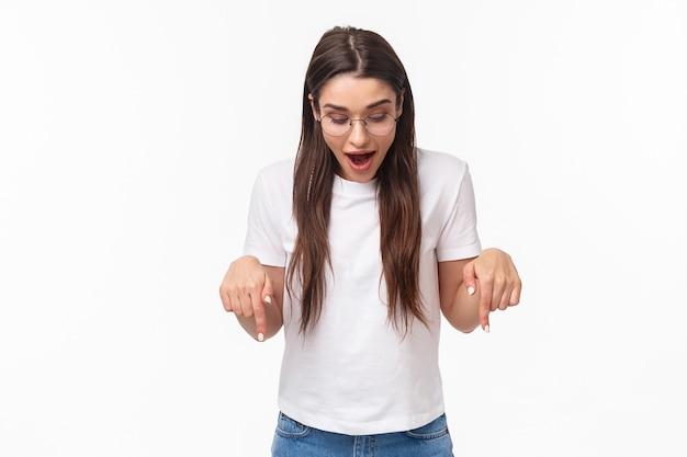 Retrato de uma mulher morena feliz espantada e curiosa com camiseta, óculos, olhando e apontando para baixo