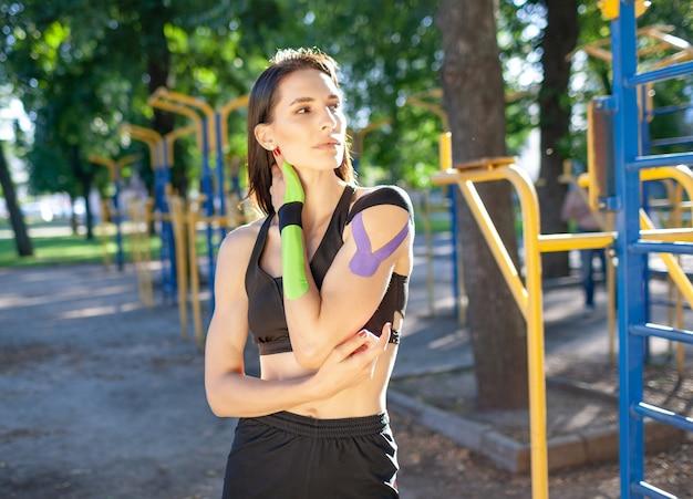Retrato de uma mulher morena musculosa e atraente usando roupa esportiva preta, olhando para o lado