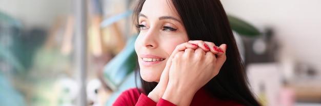 Retrato de uma mulher morena sorridente com unhas vermelhas
