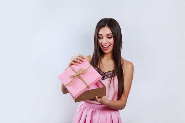 Retrato de uma mulher morena sorridente feliz abrindo uma caixa de presente rosa