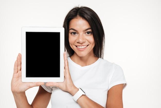 Retrato de uma mulher morena sorridente, mostrando o tablet de tela em branco