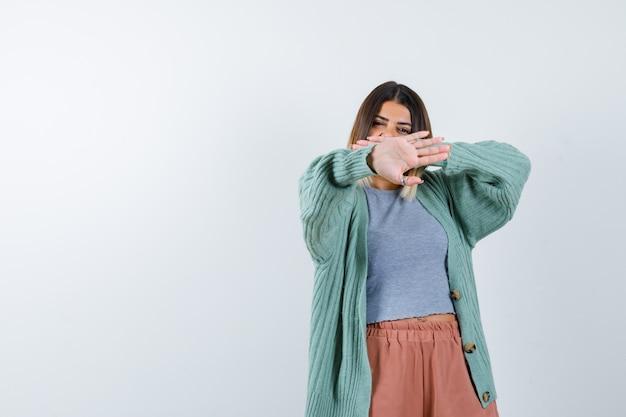 Retrato de uma mulher mostrando um gesto de parada com roupas casuais e parecendo confiante com a vista frontal