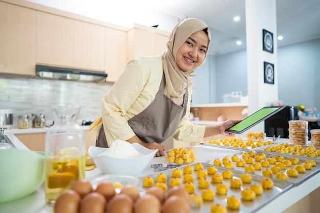 Retrato de uma mulher muçulmana feliz com um lanche de nastar na cozinha