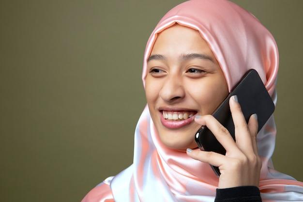 Retrato de uma mulher muçulmana usando um telefone celular