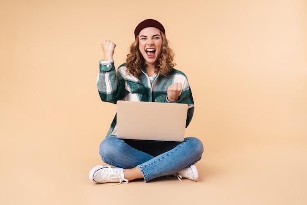 Retrato de uma mulher muito animada fazendo gesto de vencedor usando laptop enquanto está sentado no chão, isolado em bege