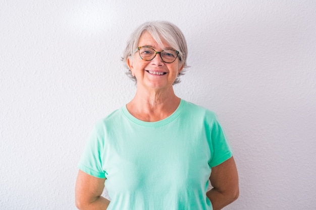 Retrato de uma mulher muito velha e madura olhando para a câmera, sorrindo e rindo - feliz senhora idosa com um fundo branco