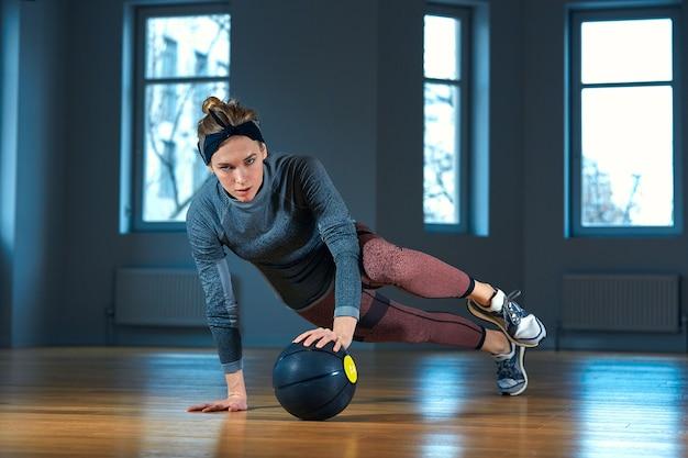 Retrato de uma mulher musculosa e em forma, fazendo exercícios de núcleo intenso com kettlebell no ginásio. feminino, exercitando-se no ginásio crossfit.