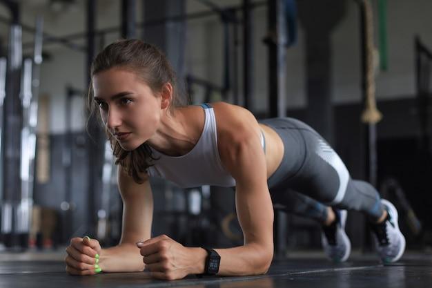 Retrato de uma mulher musculosa em uma posição de prancha.