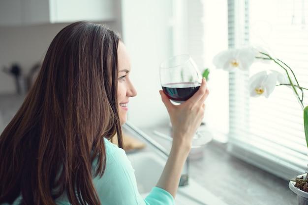 Retrato de uma mulher na janela, segurando um copo de vinho tinto
