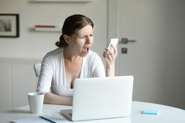 Retrato de uma mulher na mesa com laptop, olhando para o celular