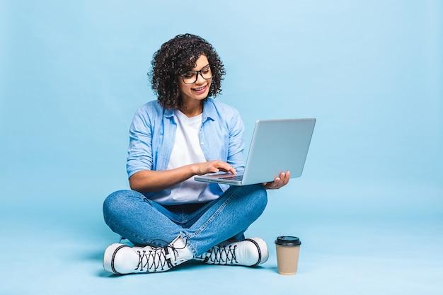 Retrato de uma mulher negra afro-americana casual sentada no chão em posição de lótus e segurando laptop isolado sobre fundo azul
