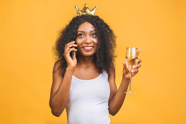 Retrato de uma mulher negra afro-americana feliz com taça de champanhe e coroa de ouro