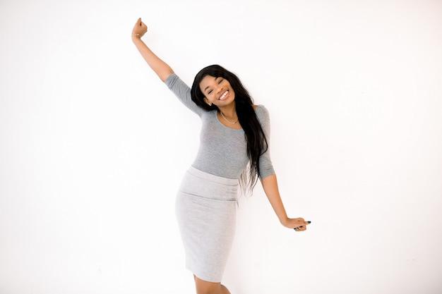 Retrato de uma mulher negra atraente vestido casual sorrindo contra fundo branco