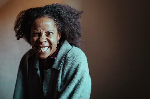 Retrato de uma mulher negra de meia-idade com uma expressão de loucura e raiva. foco seletivo do olho.