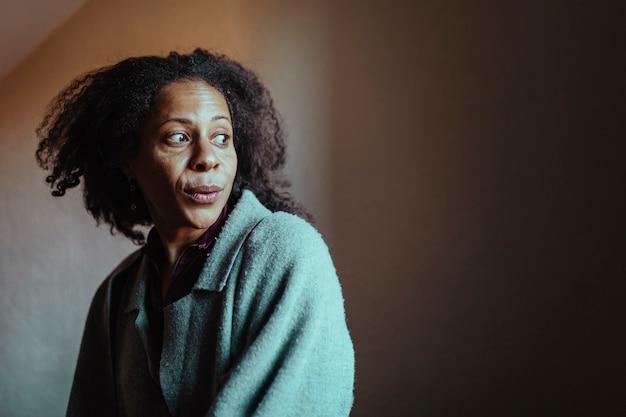 Retrato de uma mulher negra de meia-idade com uma expressão maluca, olhando para longe. foco seletivo do olho.