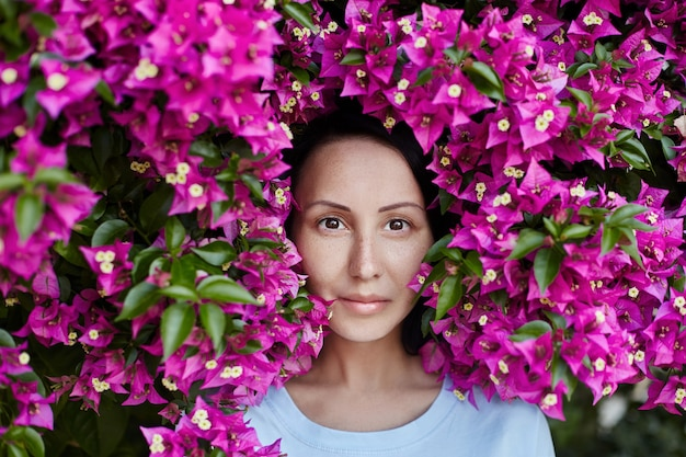 Retrato de uma mulher nos galhos de uma árvore com flores rosa vermelha, olhos castanhos