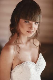 Retrato de uma mulher nova bonita. maquiagem e penteado em noiva. fechar-se. manhã de casamento. emoção suave e delicada no rosto