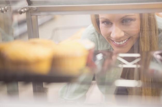 Retrato de uma mulher olhando pratos novos com pastelaria