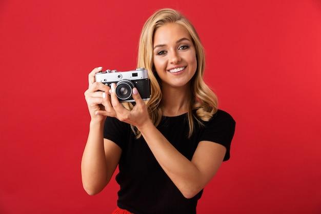 Retrato de uma mulher paparazzi 20 anos segurando e tirando foto na câmera retro, isolada sobre a parede vermelha