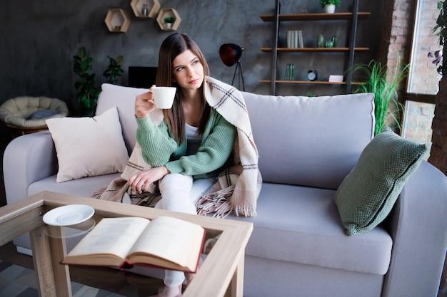 Retrato de uma mulher pensa maravilha segurar a xícara de café, sente-se no sofá em casa