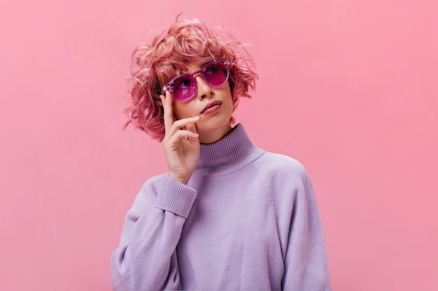 Retrato de uma mulher pensativa e encaracolada de cabelo rosa, suéter roxo e óculos de sol fúcsia, posando na parede isolada