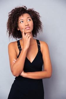Retrato de uma mulher pensativa em pé na parede cinza e olhando para cima
