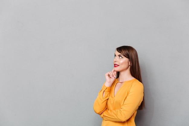 Retrato de uma mulher pensativa, olhando para longe no espaço da cópia