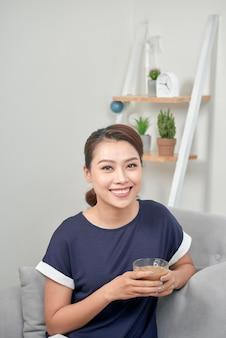 Retrato de uma mulher pensativa segurando uma xícara de café e relaxando sentado em um sofá na sala de estar em casa