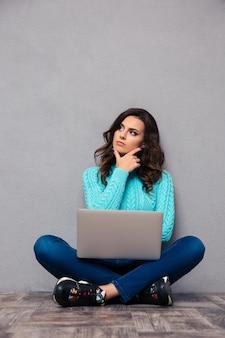 Retrato de uma mulher pensativa, sentada no chão com o laptop na parede cinza