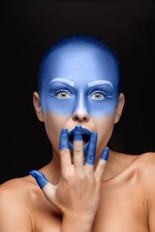 Retrato de uma mulher posando coberto com tinta azul