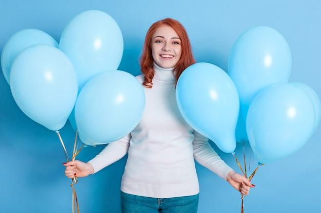 Retrato de uma mulher positiva em suéter branco e jeans, tendo muitos balões de ar azuis