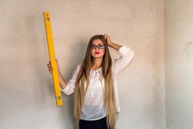 Retrato de uma mulher preocupada segurando uma ferramenta de nível de água
