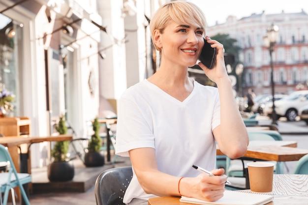 Retrato de uma mulher profissional de conteúdo, vestindo uma camiseta branca, sentada em um café de rua de verão, enquanto escreve no caderno e fala no celular