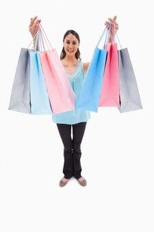 Retrato de uma mulher que mostra sacos de compras